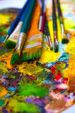 Paint brushes to the painting palette with colors on a white background