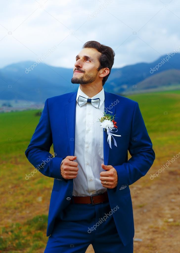439f79866e01 Mladý pohledný ženich v modré svatební oblek v horské krajině– stock obrázky