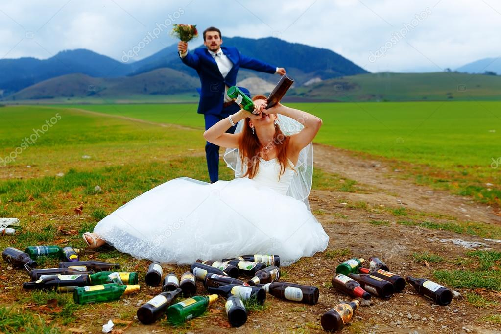 drunken bride with lots of empty beer bottles in mountain landscape  and groom comming to her- funny wedding concept.