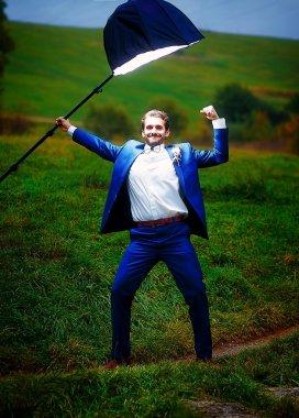 powerful groom in action hero pose under a light of stroboscope.