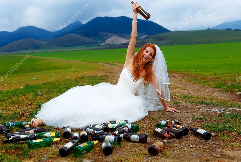 drunken bride with lots of empty beer bottles in mountain landscape - funny wedding concept.