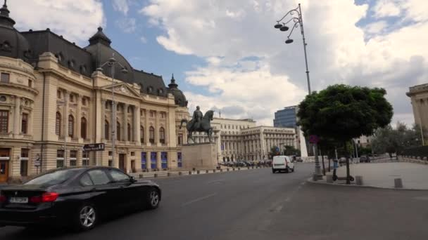 Bucharest, Romania - October 22 2020 - 4k video of The Bucharest National Central University Library Building And Statue Of King Carol I Of Romania. Travel video with cars passing by. Traffic in the city