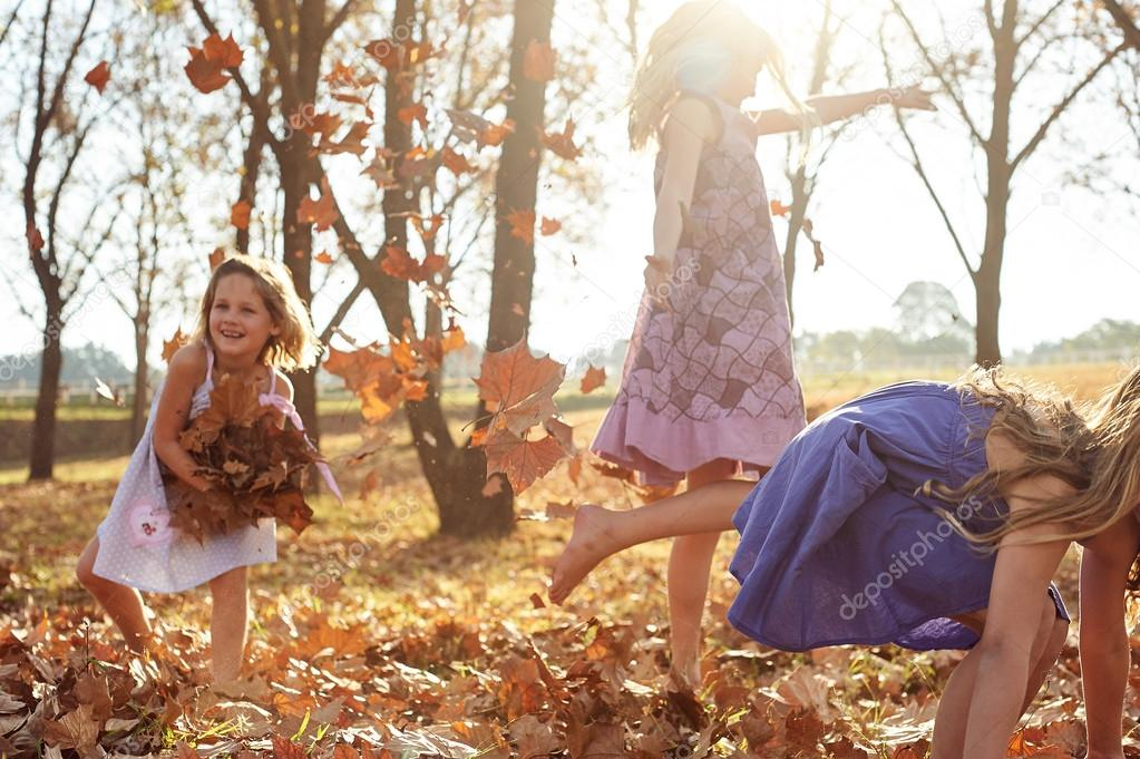 girls playing with leaves