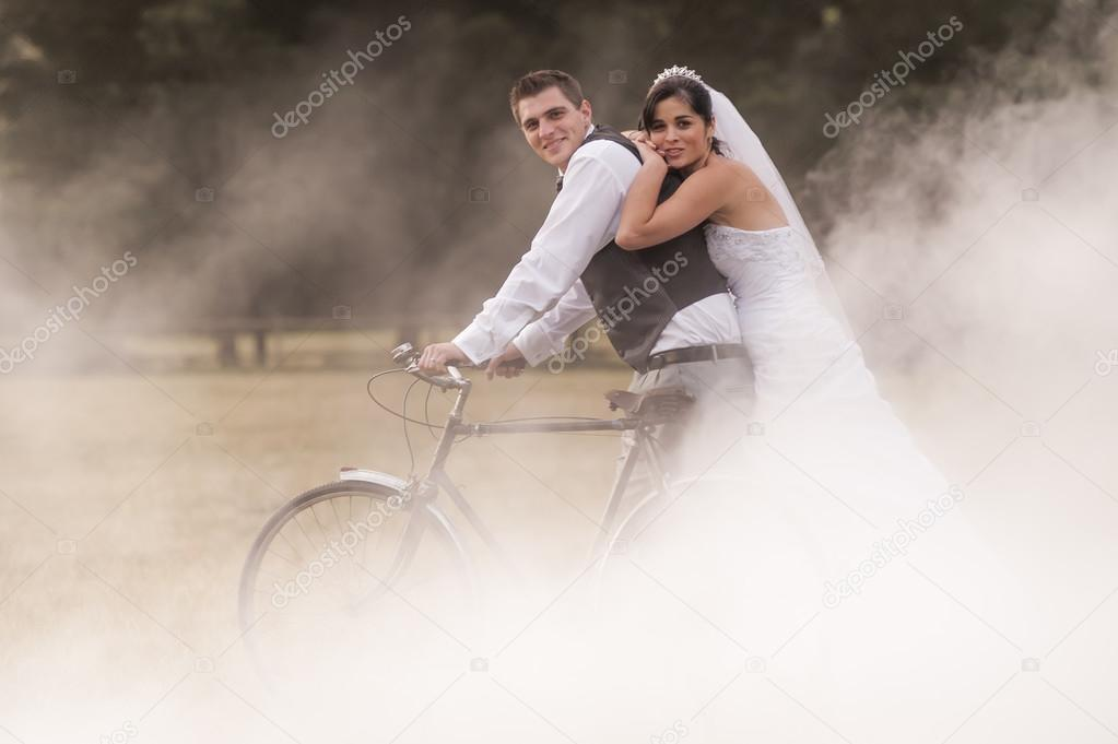 bride and groom in field with bicycle
