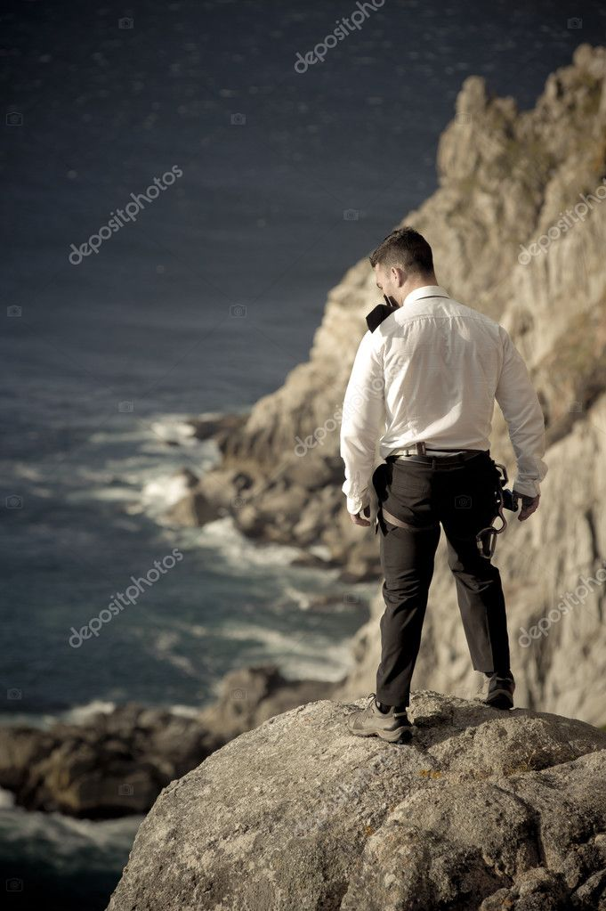 Man standing on rock and looking at ocean