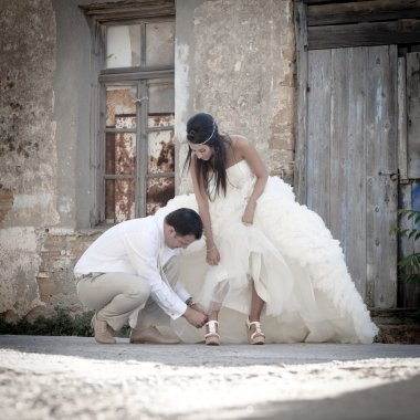 groom fixing brides shoe strap