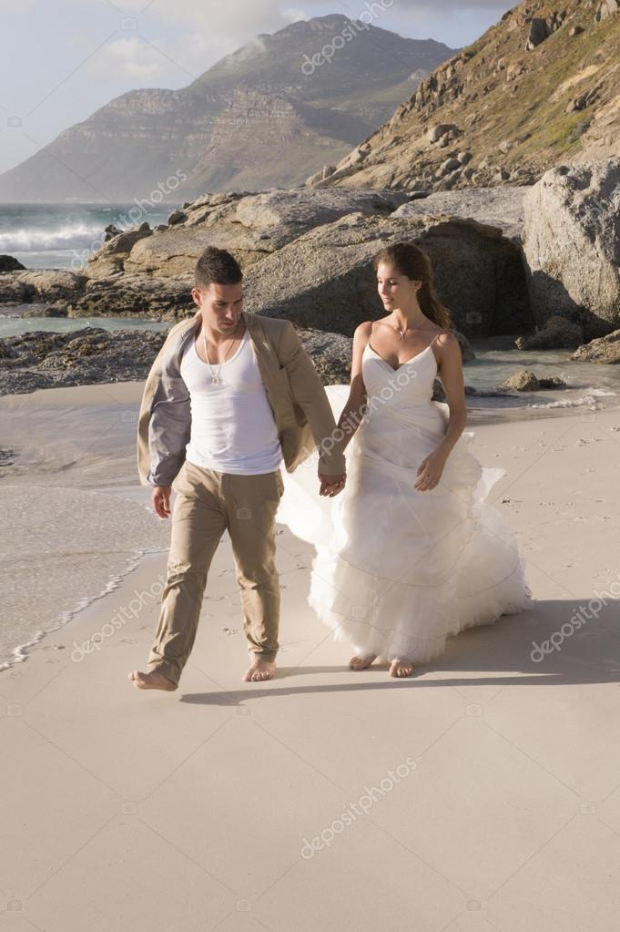 bride and groom walking at seaside