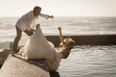 groom pushing bride in water