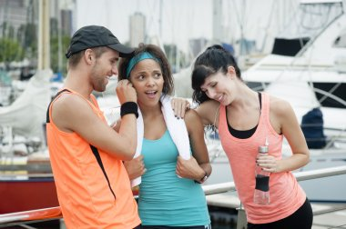 Group of young attractive runners chatting after a session of exercise