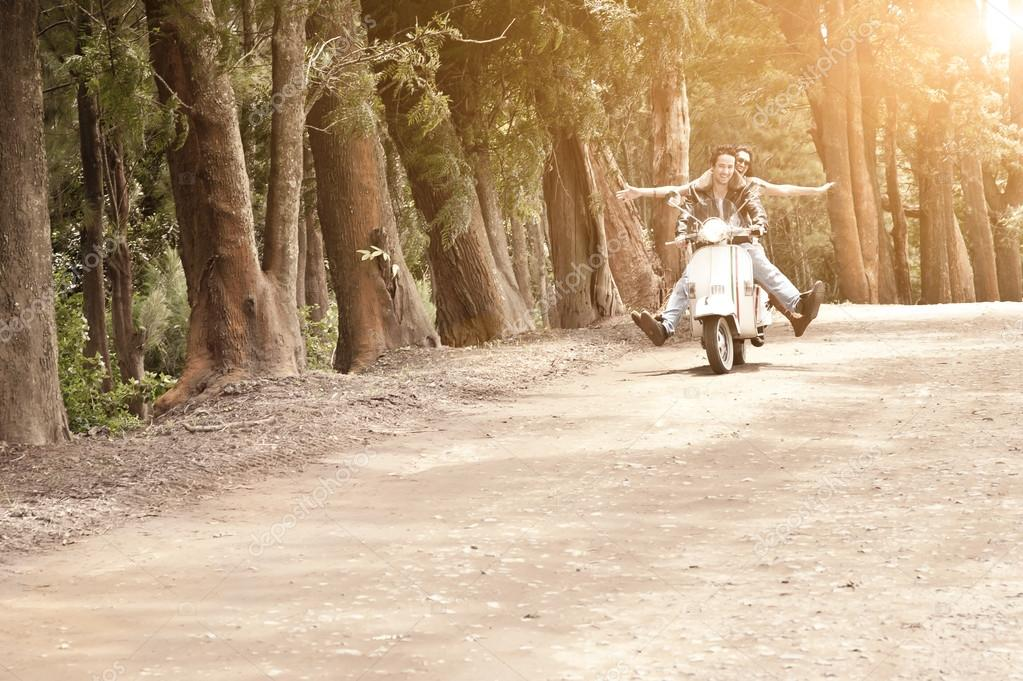 Young happy couple traveling by scooter along dirt road