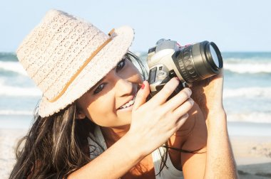 Young attractive girl taking photos with camera at beach
