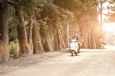Young happy couple enjoying an afternoon ride on scooter on dirt road