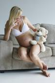 Young pregnant woman relaxing on couch with a teddy bear