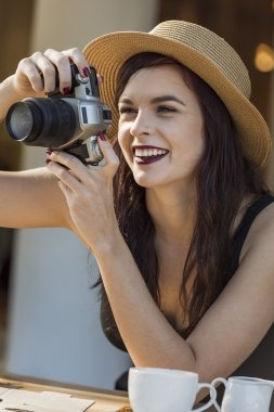 young beautiful traveler happily taking photos with camera
