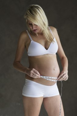Young pregnant woman measuring her abdomen
