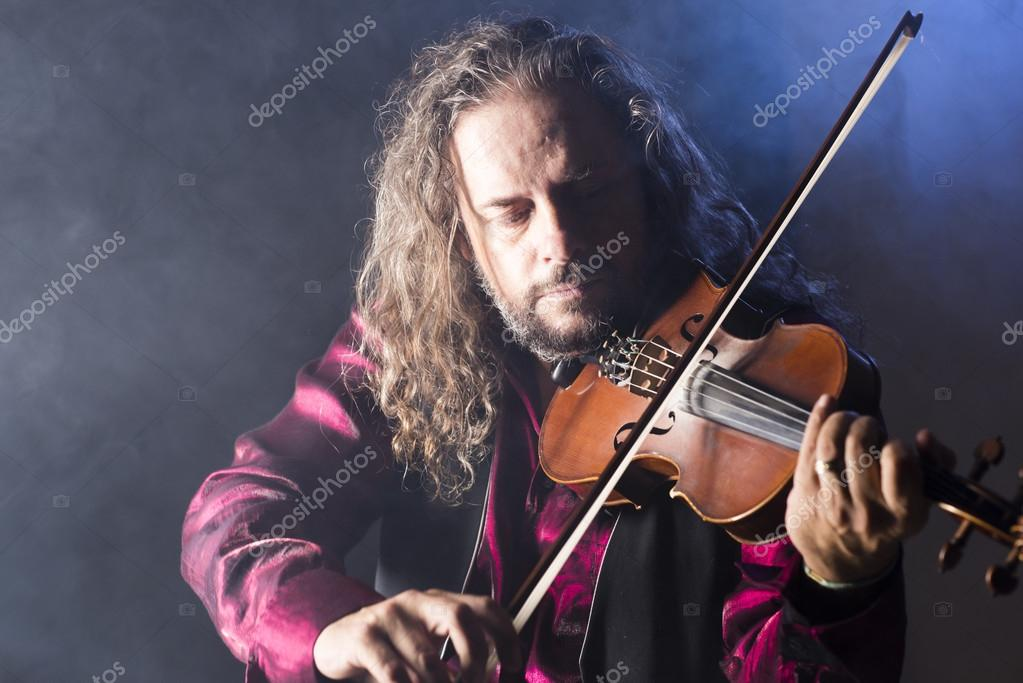 handsome man playing classical violin through blue smoke