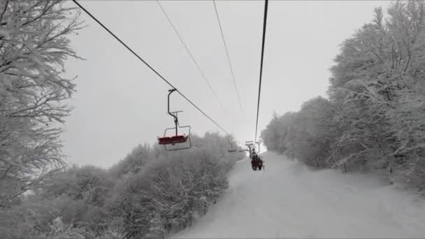 Stoupání na sedačkové lanovce se stromy pokrytými sněhem za zamračeného dne s projíždějícími sedačkovými lanovkami