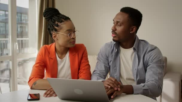 Úspěšný africký americký rodinný pár diskutovat o svých plánech pomocí notebooku doma