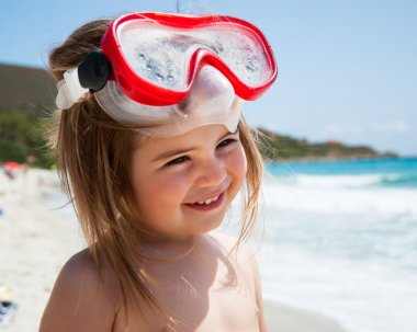 Little girl at sea with mask