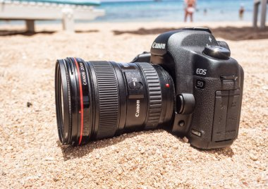 Sharm el Sheikh, Egypt - June 29, 2015: Canon 5D mark 2 interchangeable-lens professional dslr camera on the sand on the beach. Dust proof.