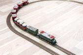 Modelu elektrický vlak na dřevěné podlaze, hra pro děti