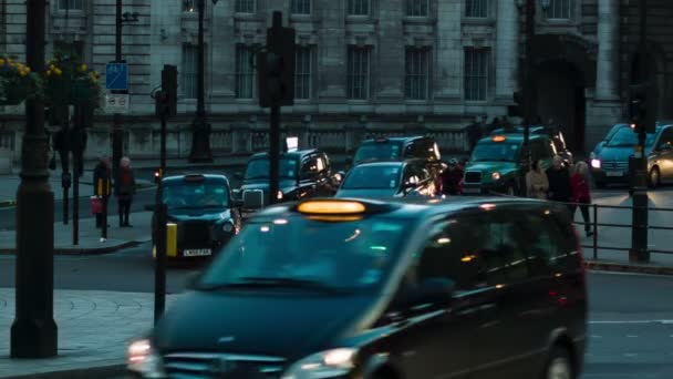Londýn - 12 listopadu 2014: Provoz na Trafalgar Square, černé taxíky, procházející