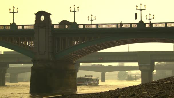 Loď prochází pod železničním mostem v noci, Londýn