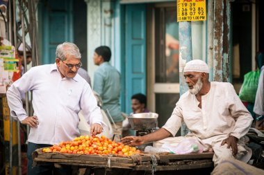 Indian man buying tomatoes on the street of Old Delhi
