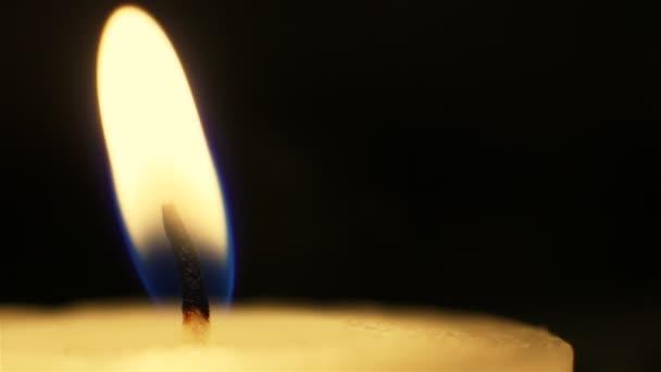 Detailní záběr na plamen svíčky na černém pozadí