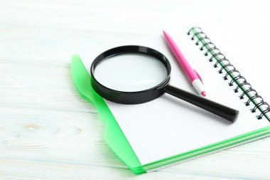 Magnifying glass with notebook and pen