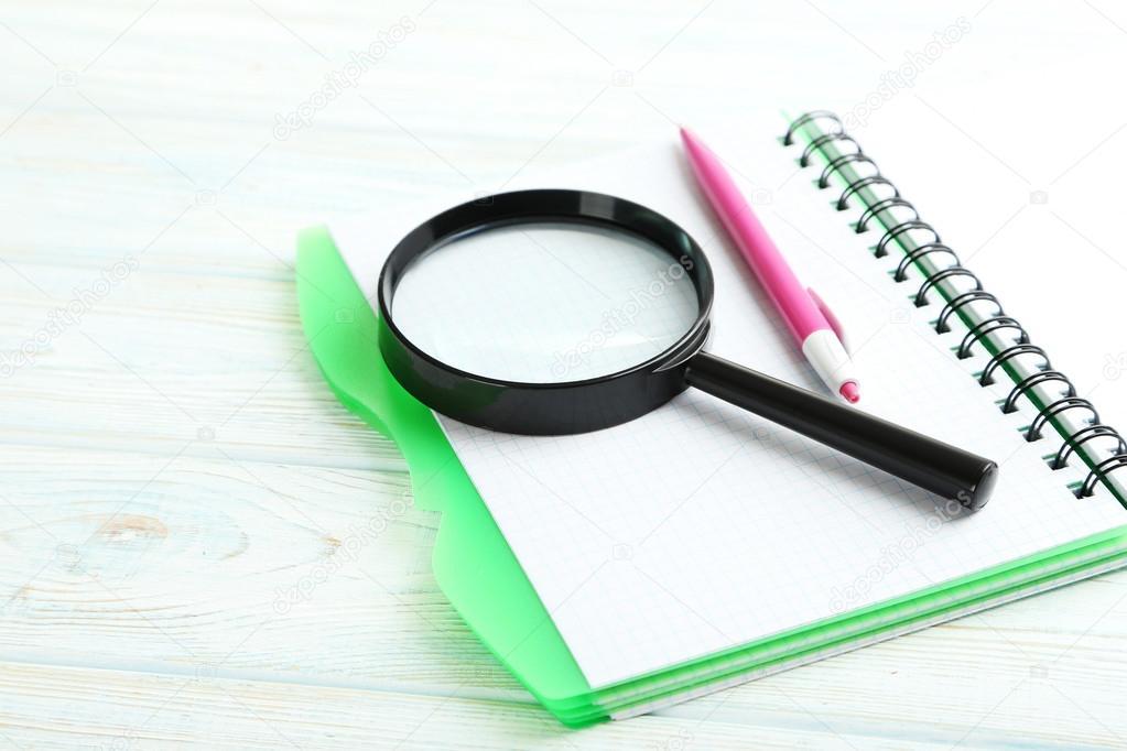 Lente di ingrandimento con il taccuino e penna foto - Specchio con lente di ingrandimento ...