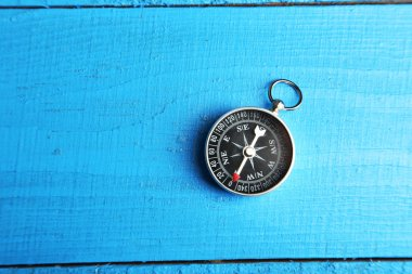 Compass on blue wooden background