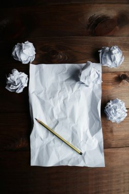 Crumpled up papers with pencil