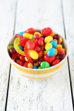 Colorful candies in bowl on wooden background
