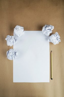 Crumpled up papers with a sheet of blank paper