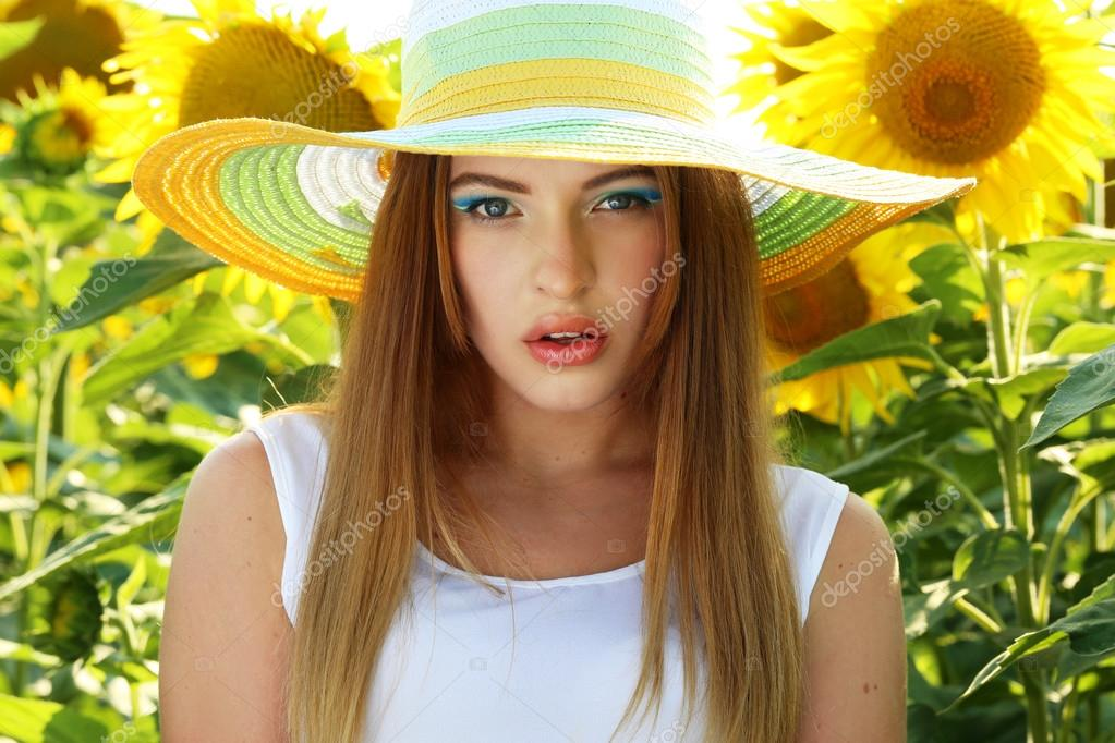 Beatiful girl with hat in the sunflowers field