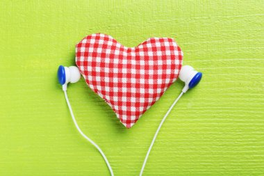 Headphones and heart on green paper background stock vector