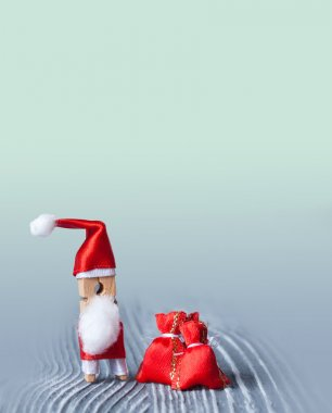 Santa Claus clothespin. Standing with a red bag of gift.