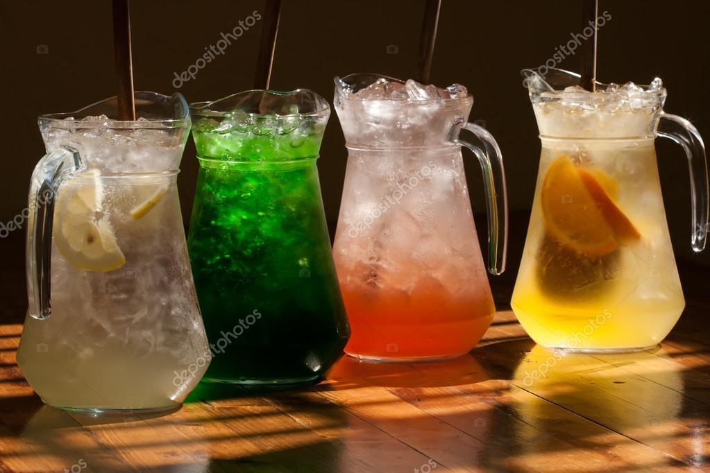 Multicolored soft drinks, lemonade in jugs. Wooden table background.