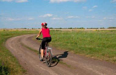 Young woman mountain bike ride on  dirt road. Ukraine