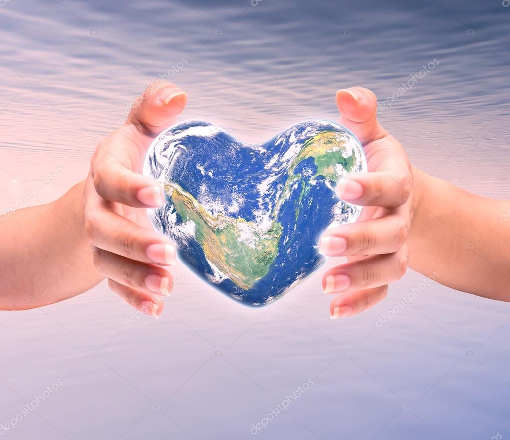 World in heart shape with over women human hands on blurred natu