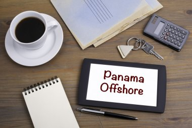 Panama Offshore. Text on tablet device on a wooden table