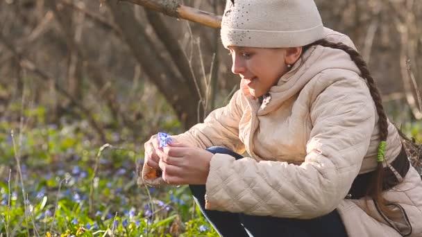 Lány összegyűjti a kék hóvirág az erdő