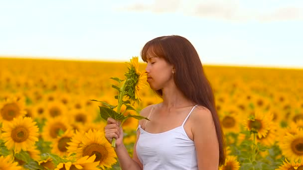 Girl smells a sunflower.