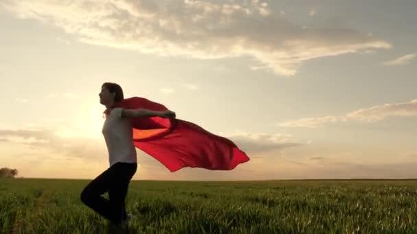 Boldog szuperhős lány, zöld mezőn fut piros köpenyben, köpenyben röpköd a szélben. Játszik és álmodik. Lassú mozgás. A tinédzser arról álmodik, hogy szuperhős lesz. fiatal lány piros köpenyben, álom kifejezés.