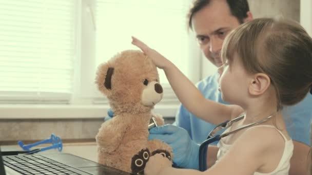 Ein kleines Mädchen spielt mit einem Teddybär und hört ihm mit einem Stethoskop zu. Kleinkind-Patient sitzt auf dem Schoß des Kinderarztes. Fürsorglicher männlicher Kinderarzt spielt mit kleinem Kind im Büro.