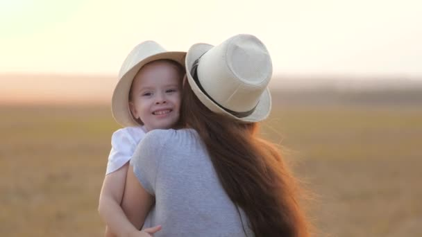 happy little daughter loves mom, child and mother hug in park. mom and baby hug. Happy family, mom and daughter in field play on grass. concept of happy family and healthy children. baby loves mommy