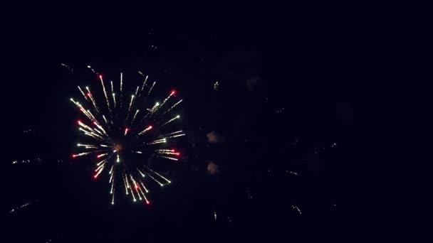 Színes éjszakai robbanások a fekete égen. Gyönyörű többszínű tűzijáték az éjszakai égbolton. Szilveszteri tűzijáték ünnepség. tűzijátékot világít bokeh fényekkel az éjszakai égen. ragyogó tűzijáték show.