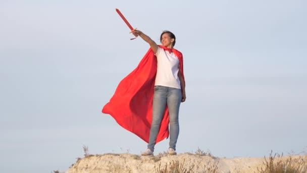 Egy spártait játszó lány. Szabad nő vörös köpenyben, karddal a kezében egy középkori lovagot játszik a hegyen. A fiatal lány szuperhősöket játszik. A lány játékkarddal harcol. kikapcsolódás és játék