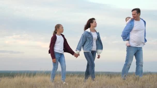 Glückliche Kinder und Eltern gehen vor dem Hintergrund des Himmels spazieren, reisen und entspannen. Glückliches Familienkonzept. glücklich lächelnde Familie Händchen haltend auf dem Feld, kleine Tochter reitet auf Papas Rücken.